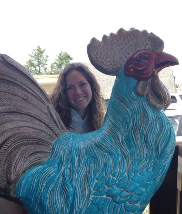 This is my sister, Rita, standing behind a giant chicken.